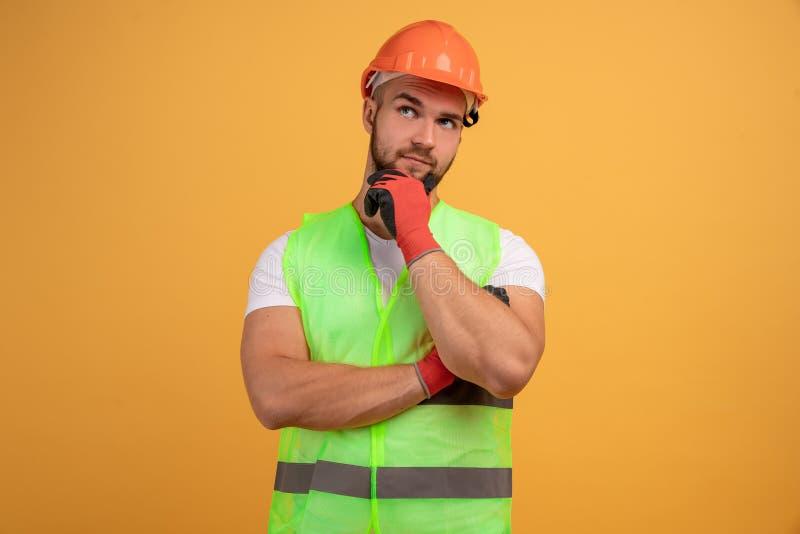El hombre pensativo de la construcción toca la barbilla, piensa en una nueva idea para la construcción, trabaja como reparador, u imágenes de archivo libres de regalías