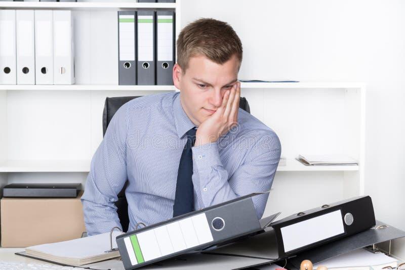 Download El Hombre Pensativo Joven Se Está Sentando Delante De Muchos Ficheros Foto de archivo - Imagen de siéntese, persona: 41906008