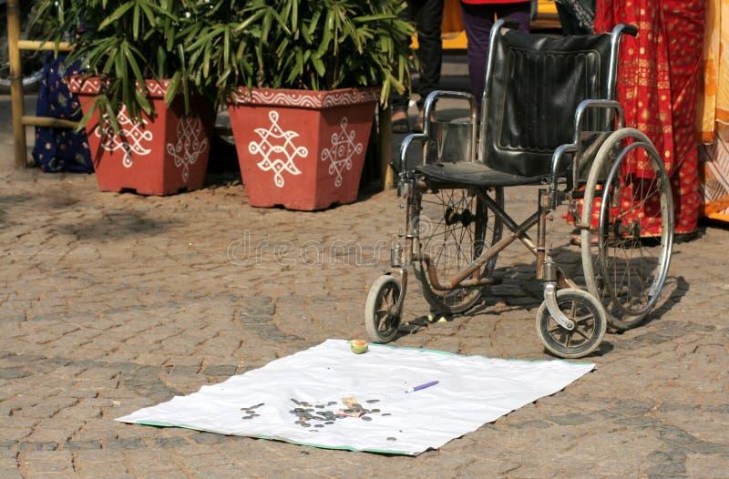 El hombre perjudicado indio coloca una silla de ruedas en un lugar público para sentar encendido y para buscar limosnas foto de archivo