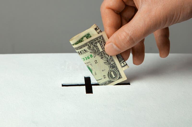 El hombre pone la donación en su mano con el dólar en ranura bajo la forma de cruz cristiana foto de archivo