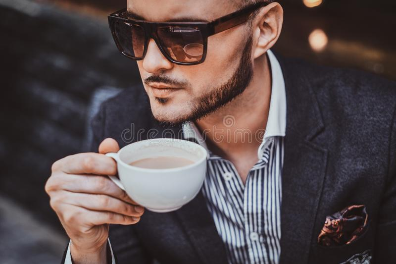 El hombre preparado alegre est? disfrutando de su coffeebreak imágenes de archivo libres de regalías