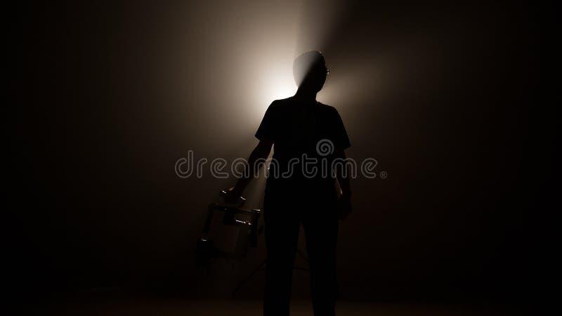 El hombre profesional oscuro de la silueta lleva a cabo el ronin de la estabilidad para la producción video de la película y hace foto de archivo