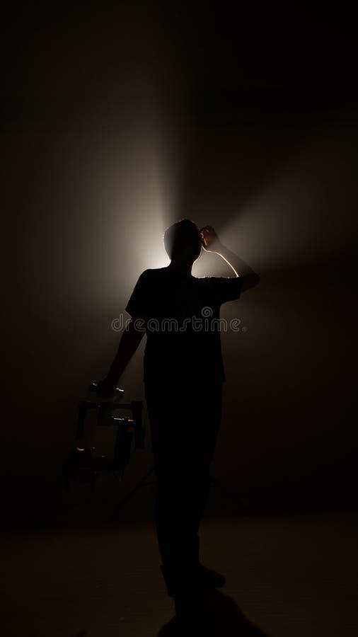 El hombre profesional oscuro de la silueta lleva a cabo el ronin de la estabilidad para la producción video de la película y hace imagen de archivo