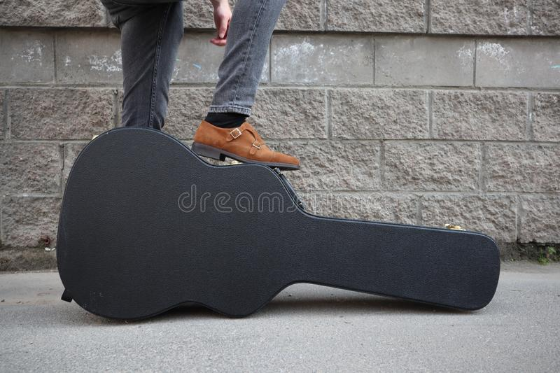 El hombre puso su pie en una caja dura de la guitarra Estuche r?gido para la guitarra el?ctrica Hombre vestido en los vaqueros qu imagenes de archivo