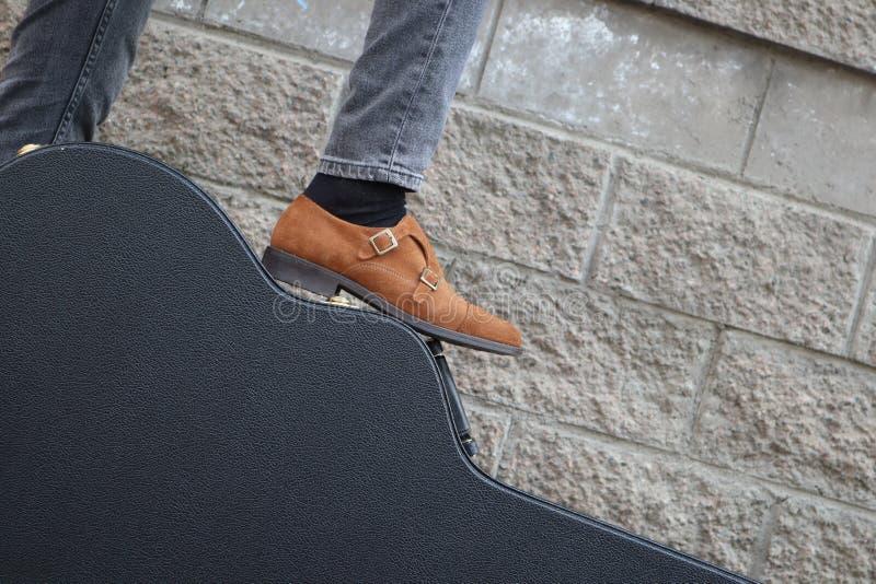 El hombre puso su pie en una caja dura de la guitarra Estuche r?gido para la guitarra el?ctrica Hombre vestido en los vaqueros qu fotos de archivo
