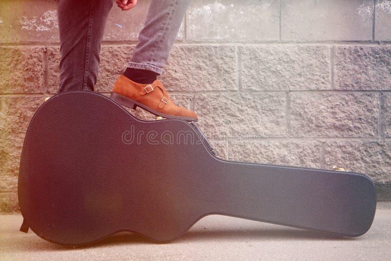 El hombre puso su pie en una caja dura de la guitarra Estuche r?gido para la guitarra el?ctrica Hombre vestido en los vaqueros qu fotos de archivo libres de regalías