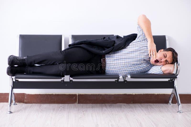 El hombre que duerme en las sillas en aeropuerto imagenes de archivo