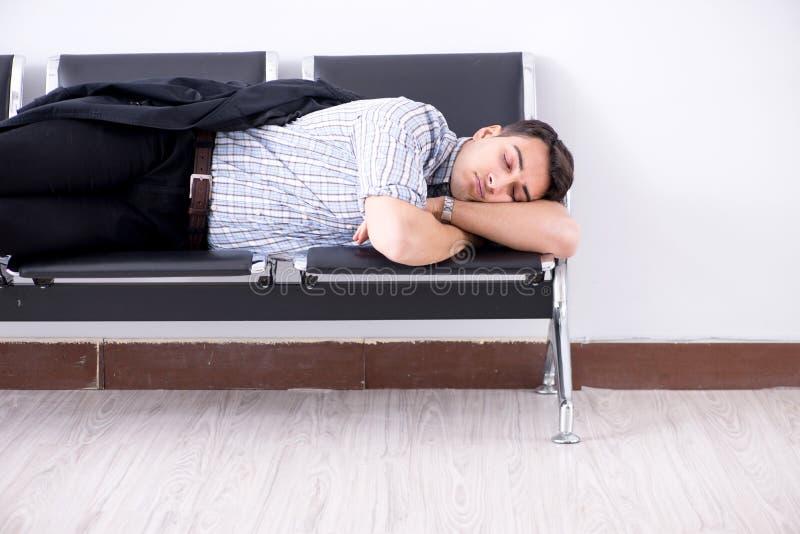 El hombre que duerme en las sillas en aeropuerto foto de archivo libre de regalías