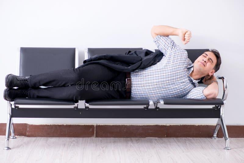 El hombre que duerme en las sillas en aeropuerto fotos de archivo