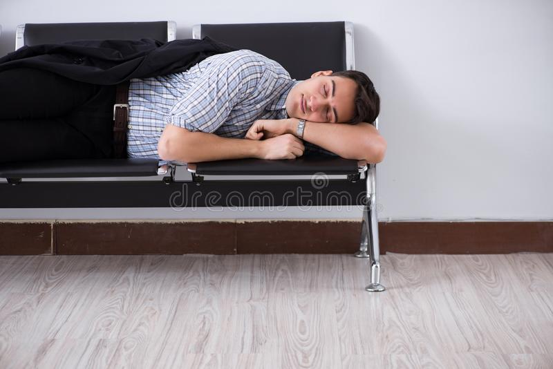 El hombre que duerme en las sillas en aeropuerto imagen de archivo libre de regalías
