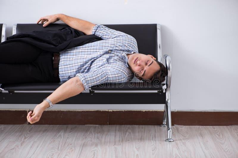 El hombre que duerme en las sillas en aeropuerto fotografía de archivo
