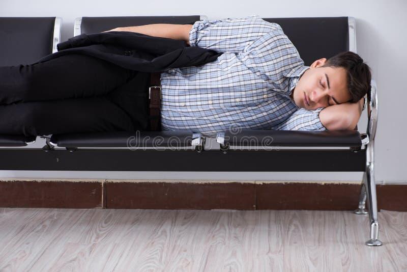 El hombre que duerme en las sillas en aeropuerto foto de archivo