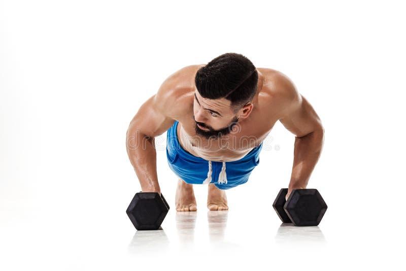 El hombre que hace ejercicios empuja hacia arriba con pesas de gimnasia imagen de archivo