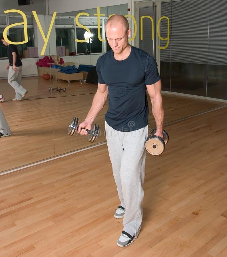 El hombre que hace el bíceps se encrespa en la gimnasia foto de archivo