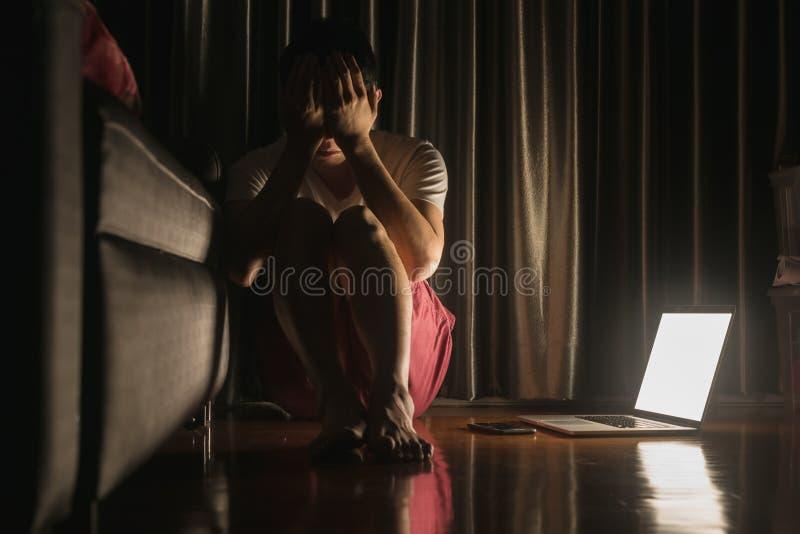 El hombre que hace frente a desorden de la depresión se sienta en piso con el ordenador portátil y smar imagen de archivo libre de regalías