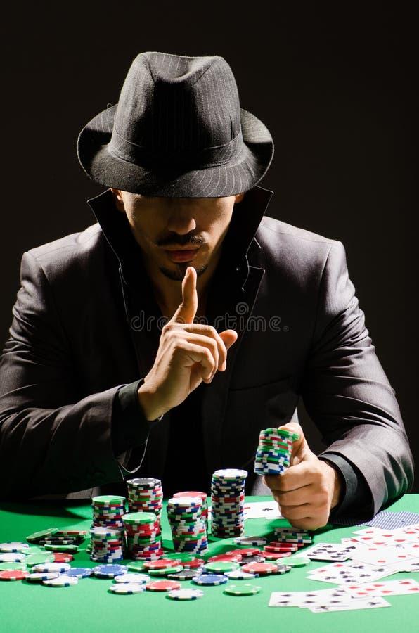 El hombre que juega en casino oscuro fotos de archivo