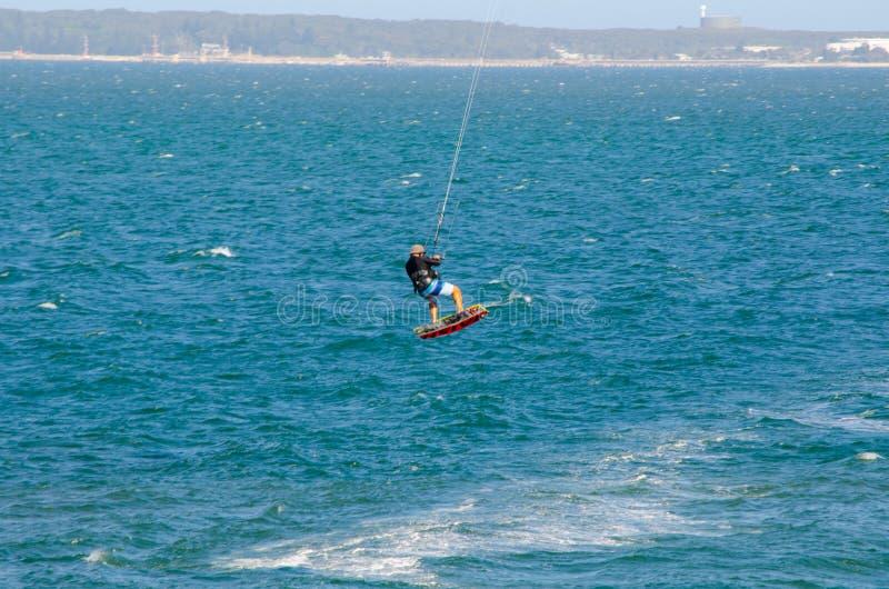 El hombre que juega la acción extrema saltando sobre la agua de mar con el tablero kitesurfing en color verde en la playa de Brig imagenes de archivo