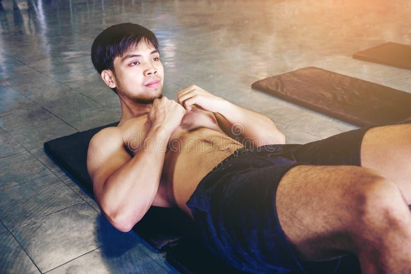 El hombre que la ejecución se sienta para arriba ejercita los músculos en el entrenamiento de la aptitud en g fotos de archivo