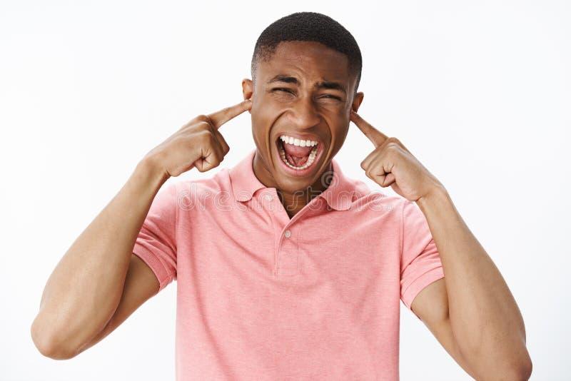 El hombre que lanza la tensión no puede manejar ruido de la ciudad Oídos de cierre descontentados y cansado del individuo afroame fotografía de archivo