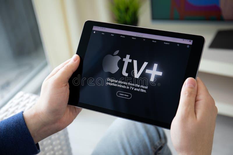 El hombre que lleva a cabo el iPad con el app de Apple TV proporciona fluir películas imagen de archivo libre de regalías