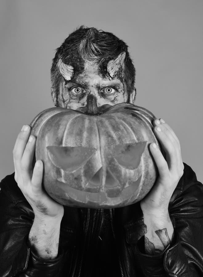 El hombre que lleva maquillaje asustadizo sostiene la calabaza en fondo rojo El demonio con los cuernos y los controles ocultados fotografía de archivo