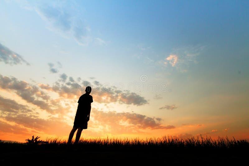 El hombre que mira a la puesta del sol en el cielo con esperanza de la metáfora de la tristeza fotografía de archivo libre de regalías