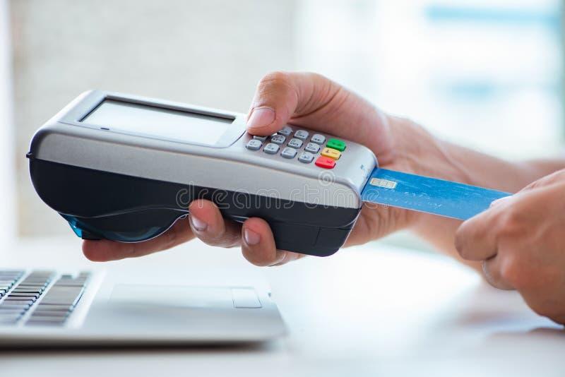 El hombre que procesa la transacción de la tarjeta de crédito con el terminal de la posición imagen de archivo libre de regalías