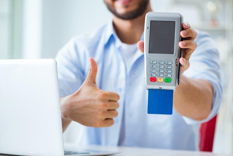 El hombre que procesa la transacción de la tarjeta de crédito con el terminal de la posición imagen de archivo