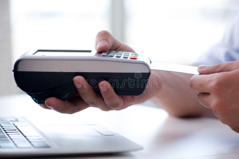 El hombre que procesa la transacción de la tarjeta de crédito con el terminal de la posición imagenes de archivo