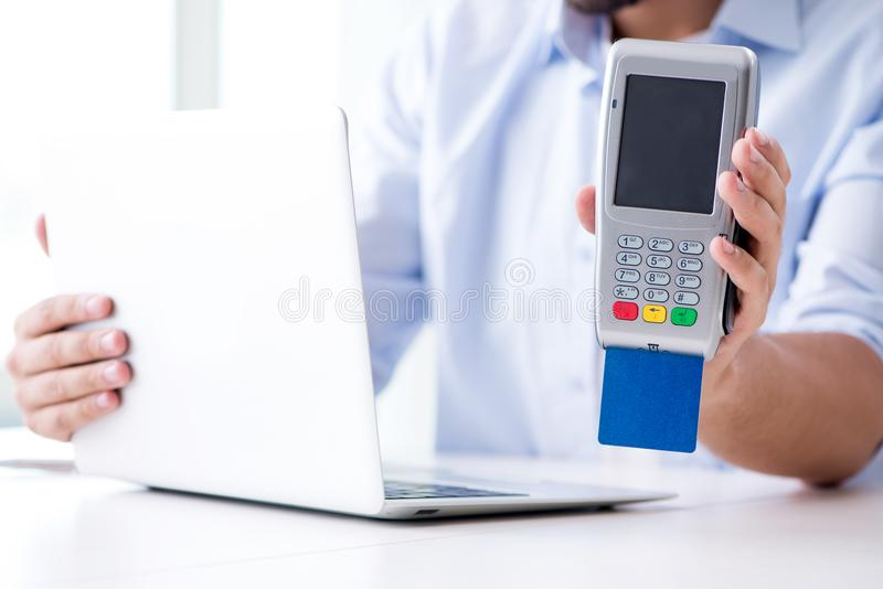 El hombre que procesa la transacción de la tarjeta de crédito con el terminal de la posición fotos de archivo