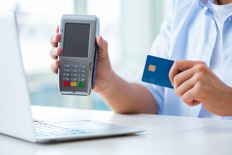 El hombre que procesa la transacción de la tarjeta de crédito con el terminal de la posición foto de archivo