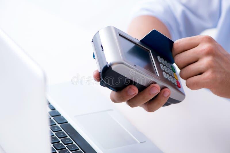 El hombre que procesa la transacción de la tarjeta de crédito con el terminal de la posición fotografía de archivo libre de regalías
