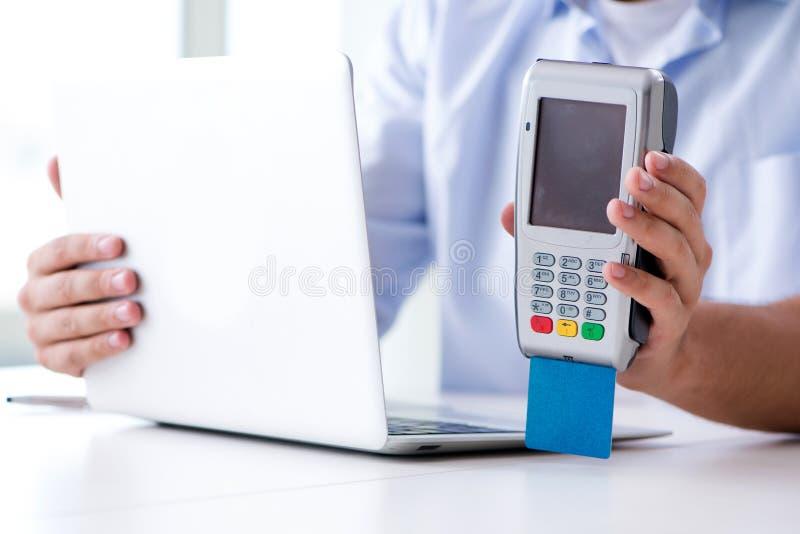 El hombre que procesa la transacción de la tarjeta de crédito con el terminal de la posición fotos de archivo libres de regalías