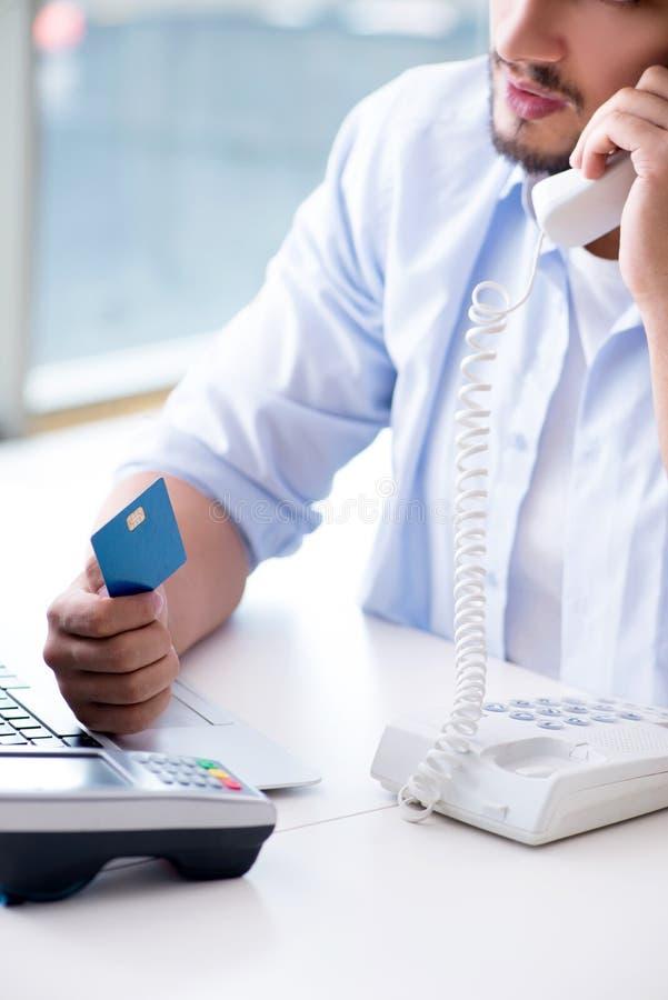 El hombre que procesa la transacción de la tarjeta de crédito con el terminal de la posición foto de archivo libre de regalías