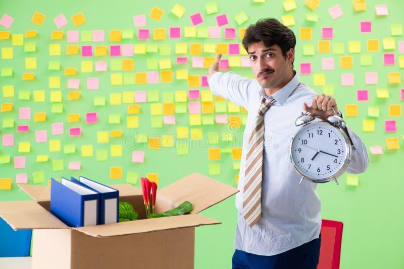 El hombre que recoge su materia después de redundancia en la oficina con concepto en conflicto de la gestión de muchas prioridade imagenes de archivo