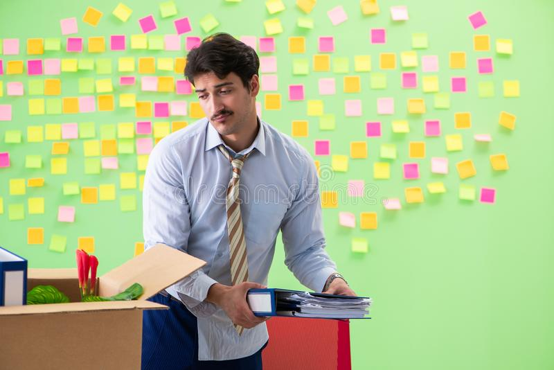El hombre que recoge su materia después de redundancia en la oficina con muchas prioridades en conflicto fotos de archivo libres de regalías