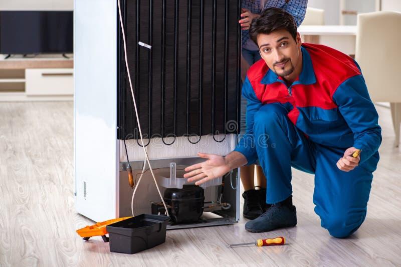 El hombre que repara el refrigerador con el cliente foto de archivo libre de regalías