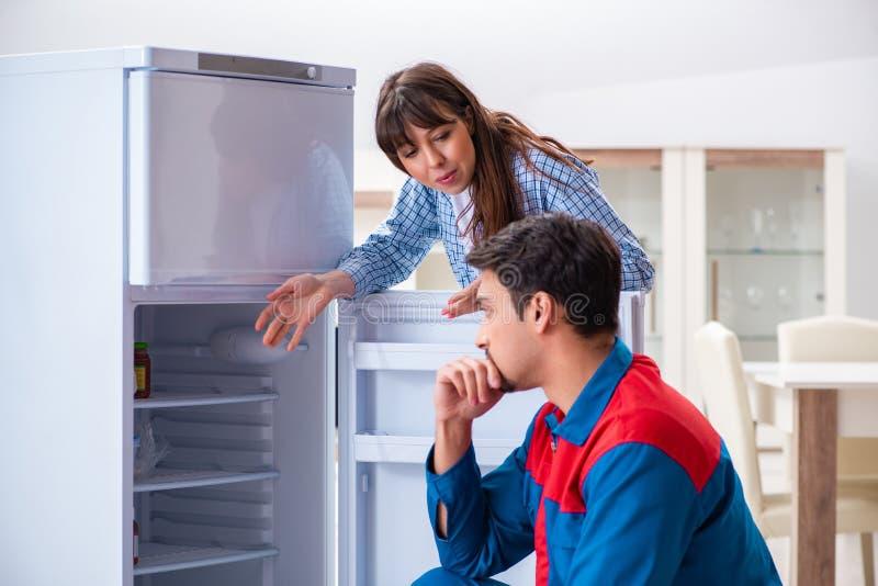 El hombre que repara el refrigerador con el cliente foto de archivo