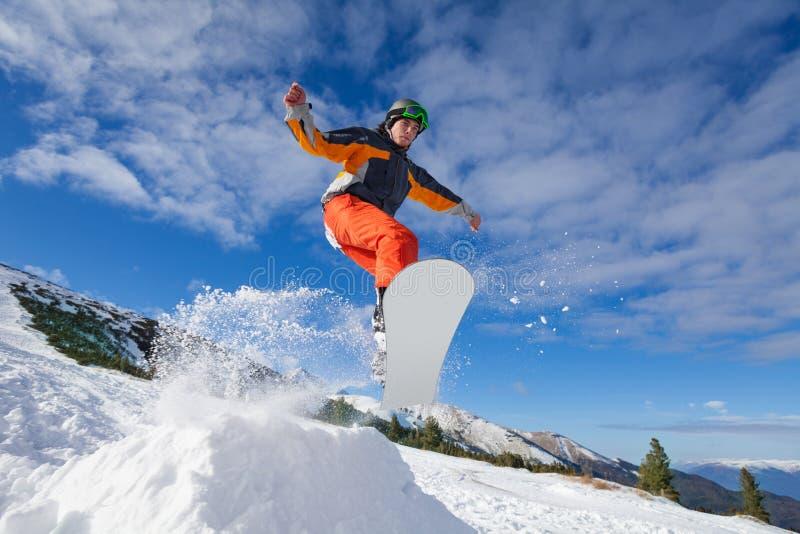 El hombre que salta con la snowboard de la colina de la montaña imagen de archivo