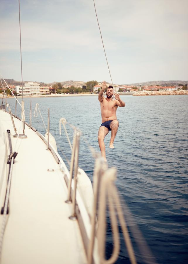 El hombre que salta del barco de navegación en el mar imágenes de archivo libres de regalías