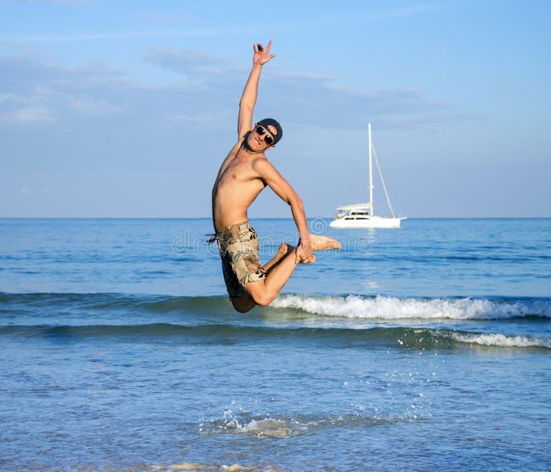 El hombre que salta en la playa foto de archivo libre de regalías