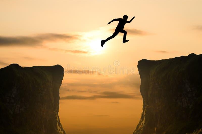 El hombre que salta sobre el acantilado, silueta fotografía de archivo