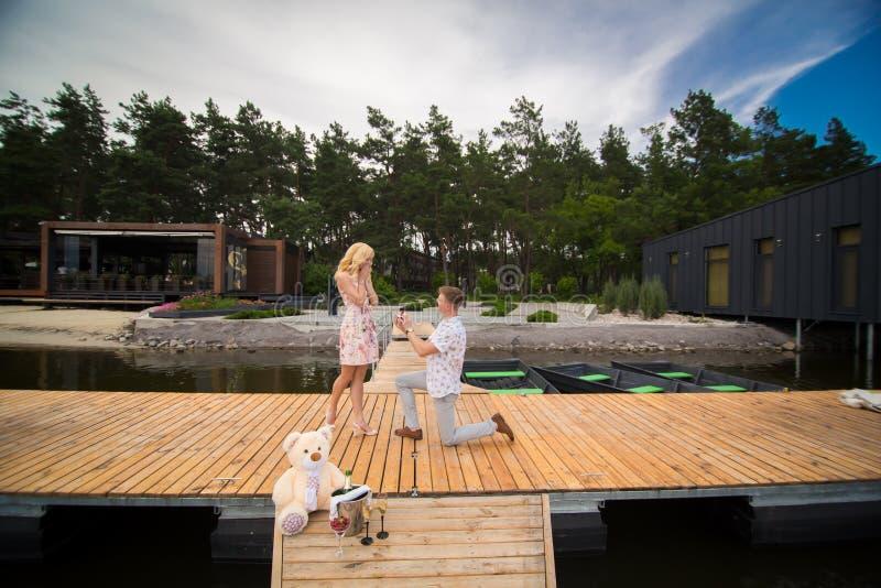 El hombre que se coloca en un embarcadero en la rodilla hace una propuesta de matrimonio foto de archivo