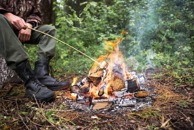 El hombre que se sienta por el fuego en el bosque fotografía de archivo libre de regalías