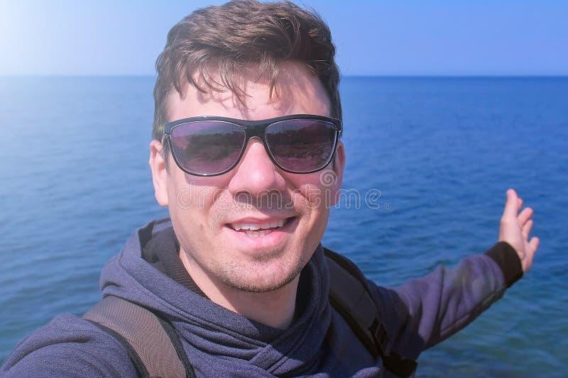 El hombre que el smartphone video del selfie de las charlas en ondas de la playa del mar da saluda y sonríe foto de archivo libre de regalías