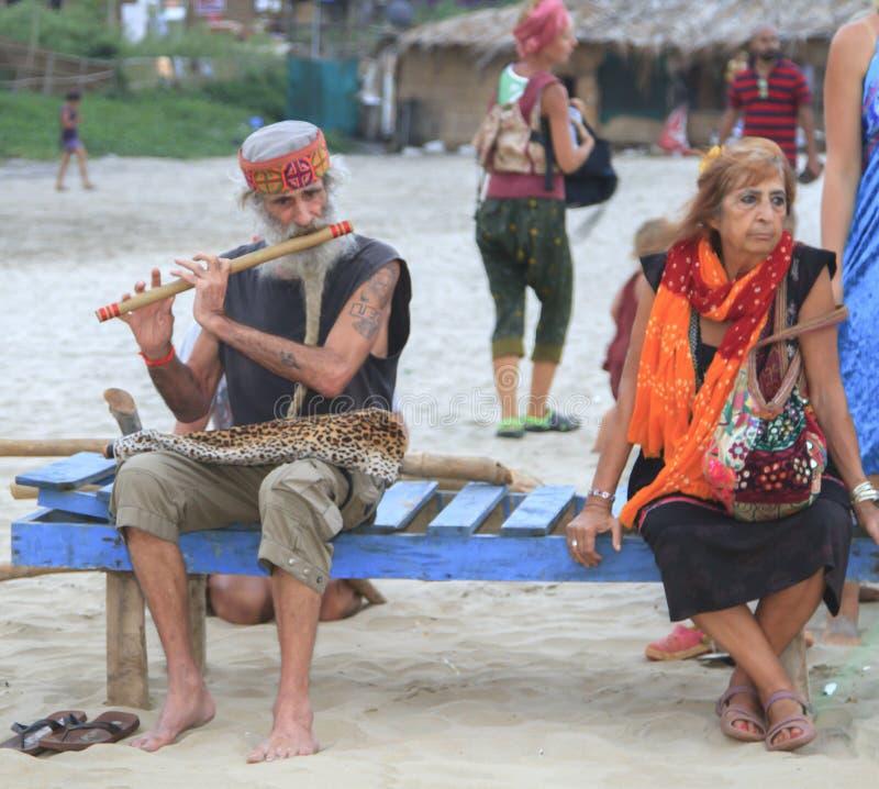 El hombre que toca la flauta que se sienta en la playa en la compañía de imágenes de archivo libres de regalías