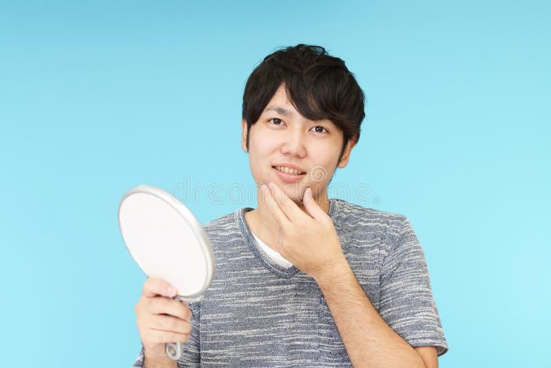 El hombre que toma cuidado de su cara imagen de archivo libre de regalías