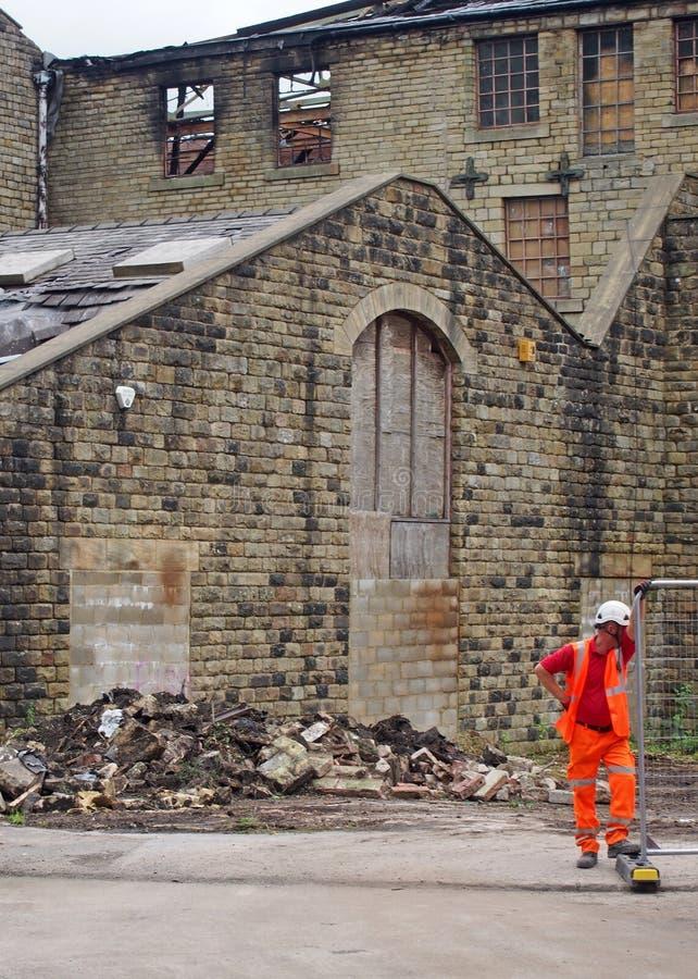 El hombre que trabaja en la demolición del edificio del molino de los walkeys adentro hebden el puente después del fuego en el 1r fotografía de archivo