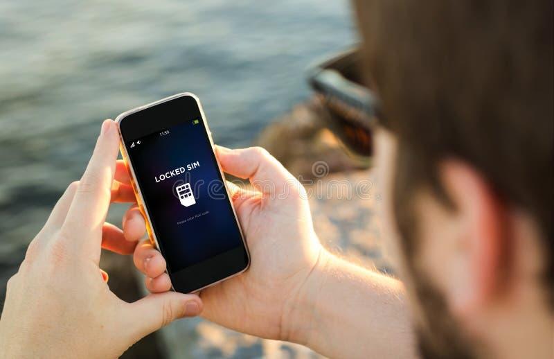 El hombre que usaba su teléfono móvil en la costa cerró el sim fotografía de archivo