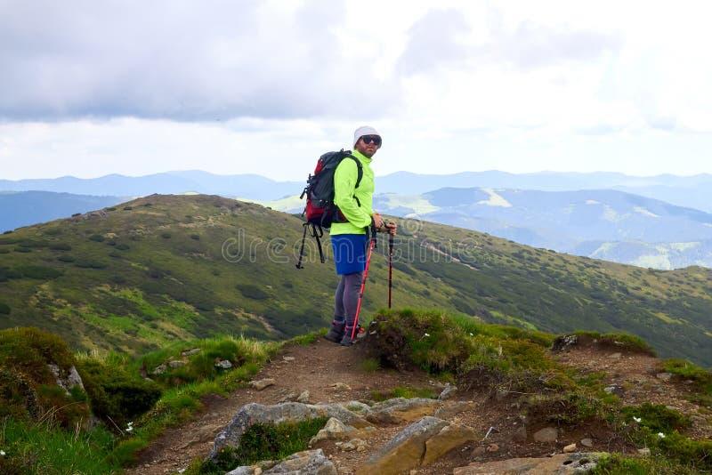 El hombre que viaja con la mochila que camina en montañas viaja las vacaciones activas de la aventura del concepto del éxito de l imágenes de archivo libres de regalías